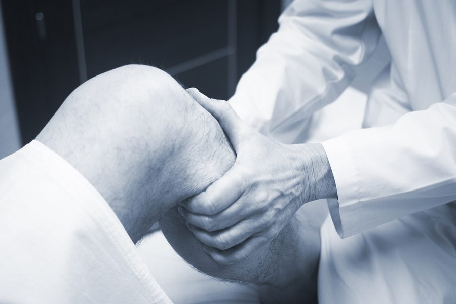 Traumatologist orthopedic surgeon doctor examining middle aged man patient to determine injury pain mobility and to diagnose medical treatment in leg knee meniscus cartilage ankle and foot injury.